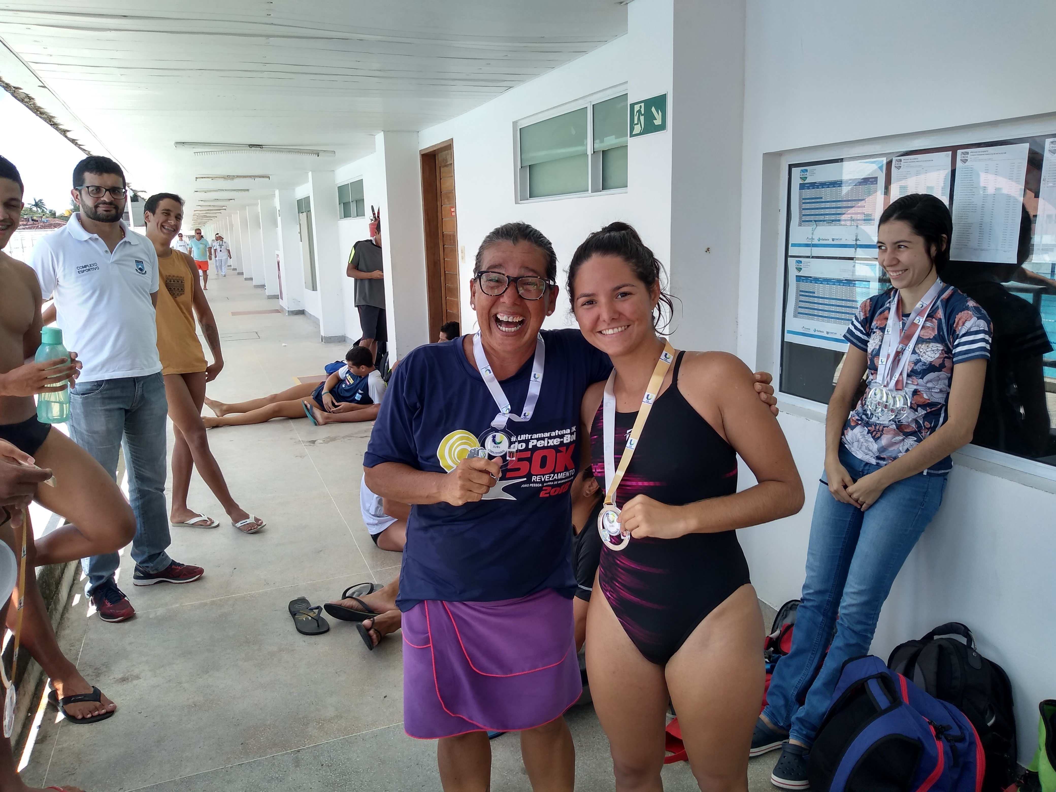 A atleta Natália Maria Câmara Luna (à direita,  3 medalhas  de ouro e 1 de bronze), dividindo a conquista dos 50 m peito com sua colega de equipe Maria Manuela Chaves Figueiredo (à esquerda, medalha de prata).